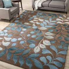 This hand-tufted rug adds comfort, style, and color to your home. The rich background of this mocha rug blends well with many decorative color schemes, while the variegated blues of the abstract flora