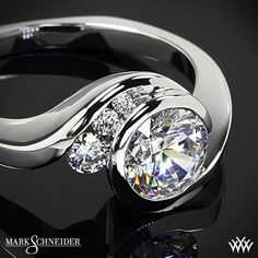 Mark Schneider Escape Solitaire Engagement Ring is sure to add a bit of whimsy to your day to day. The bezel set center diamond is accented with 3 channel set Round Brilliant Diamond Melee which graduate in size.