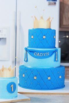 Prince cake, put smaller cake on top, 4 tier cake. Royal blue, mint, & gold. Add ribbon under each tier