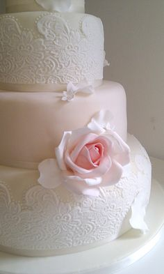 Lace Mould Wedding Cake  Pretty tiers decorated with a lace mould technique. Bespoke Moulds can be made using a swatch of lace from your dress.  Finished with pink and ivory roses and piped pearl necklaces.  Price as shown  £565