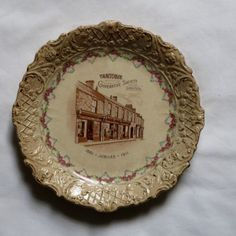 Material: Clay, glaze. Height: 2.5cm Diameter: 24cm In the centre is a brown transfer print showing a terrace with shop front.
