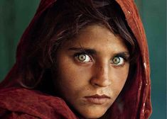 """Afghan Girl by Steve McCurry for National Geographic (June 1985) """"I WILL NEVER KNOW THIS WOMAN'S NAME. Among Afghan villagers it is the custom for women not to tell their names to strangers. On this cold November night she is busily preparing food for the six mujahidin, Afghan freedom fighters..."""""""