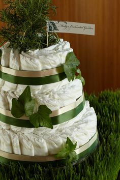 Garden-Themed Diaper Cake. Three-tiered diaper cake with 100 HUGGIES® Pure & Natural Diapers, green ribbon, faux ivy and topped with a potted rosemary plant to remember the event for years to come.