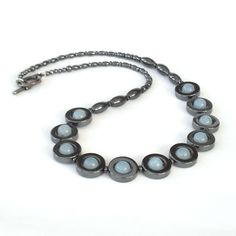 SALE: Handmade necklace with soft blue jade & hematite £10.00 Pretty gentle blue semi-precious jade beads sit within 16 mm polished hematite rounds.  I have used smaller round and rice shaped hematite beads to complete this unique necklace. The result is a wonderfully captivating necklace that is bound to draw many compliments.  Designed by Sue Mellem in Northamptonshire, April 2014