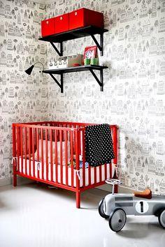 Stoere babykamer met rode accenten en op de muur de vrolijke huisjes van Sandberg kinderbehang Kaspar (verkrijgbaar via www.juniorssuite.com)