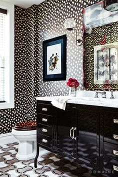 This bathroom's bold pattern-on-pattern mix works, thanks to its restricted color palette and elegant, glossy surfaces.