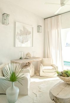 Beautifully designed white beach style room is furnished with white slipcovered club chairs placed on a white plank floor flanking a driftwood console table positioned beneath a sea fan in a white shadow box lit by whitewashed wall sconces and natural light from a window dressed in white curtains.
