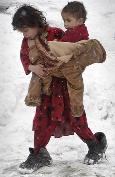 An Afghan refugee girl carries her sister around their camp during a snowstorm…