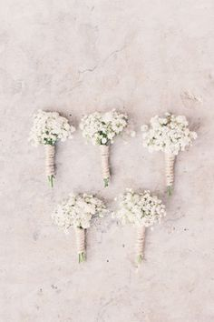 Collection of baby's breath boutonnieres for groomsmen at vintage wedding.