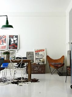 mmm - radiator, old posters, ceiling lamp, table with odd chairs and old suitcase!