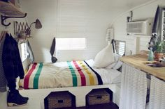 inside 1962 Shasta camper. Fresh white paint. Double bed with built-in storage below.