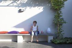 Trendy tuin door betonnen bank geintrigeerd in de betonnen strakke tuinmuur