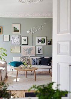 Tipp für grüne Wandfarbe. Modernes Wohnzimmer mit weißer Couch und schönem Bilder Arrangement über dem Sofa - toll passend zur hohen Decke mit weißem Struck. Kombination aus Alt und Neu