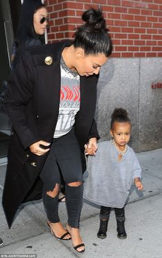 Fashion forward: North West was dressed like her rapper father Kanye West, in a gold chain and baggy monochrome top as she held mom Kim Kardashian's hand on Monday