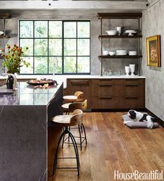 """Dark, wire-brushed oak cabinets, cement plaster walls, marble counters, and sand-cast bronze hardware — """"There's a sense of comfort that comes from the rustic materials,"""" says Patrick Sutton, who designed this kitchen in the Maryland countryside. """"The look is part farmhouse and part industrial, with that great trussed ceiling and a large steel window we found in a salvage yard. But everything is detailed in a modern way."""""""