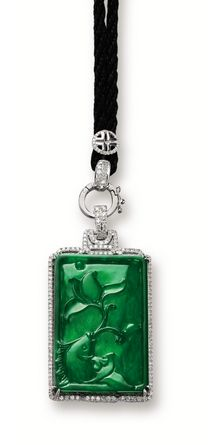 JADEITE AND DIAMOND 'FISH' PENDANT Suspending a jadeite plaque of intense emerald green colour and good translucency, carved with a lotus flower and a carp, symbolising abundance and affluence, framed by brilliant-cut diamonds extending to the hook surmount, mounted in 18 karat white gold.