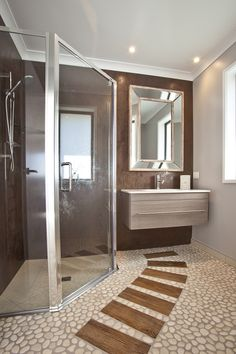Wooden boards, over pebble look flooring, step you through to the hand basin of this resort style ensuite bathroom.