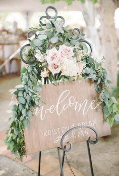 welcome wooden wedding sign with roses and greenery leaves