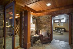 Brick walls give this sitting area a cozy feel between the wine cellar & home gym.