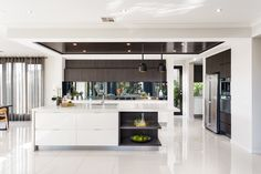 KITCHEN: The kitchen is simple and elegant in colour. Light polished porcelain tiles line the floor of this style, whilst the dark timber features in the cabinetry are used to enhance the bold oversized pieces of furniture in the home. visit our Black Label Lookbook style here: http://www.metricon.com.au/get-inspired/lookbook/black-label