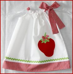 Description... This listing is for the super cute Counrtry Chic Strawberry pillowcase style side bow dress. The dress was a made with a white cotton fabric and paired with a red gingham and features a sweet red strawberry applique. This dress would be perfect for summer pictures :) The...