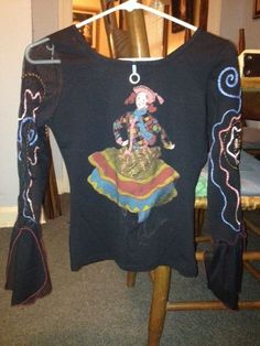 "On eBay: Medium long sleeve black shirt with multi-color stitch embroidery. Sleeves have sheer ruffles at the bottom 6"" of the left sleeve and the right sleeve is sheer up to the shoulder. 15"" across from shoulder seam to seam and 20 1/2"" from shoulder to bottom hem. Whimsical picture on back with Save the Queen written across the bottom of the artwork. in a red script. Made in Italy"