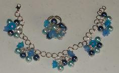 Parure: anello e braccialetto con perle e fiori di lucite nei toni dell'azzurro.