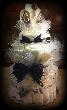Bridal shower cake made from 2 large bath towels, 4 handtowels, 12 washcloths and 12 dishwashing cloths (bar cloths) and kitchen utensils