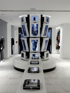 """This custom suit maker stitches together digital elements and clean lines for a clutter-free buying experience. This is the Digital mannequin: Created by streaming together a series of still photographs, this 20-LCD screen display features five live-action models wearing seasonal suits. The high-res images allow customers to see such detailing as types of buttons, fabric and stitching. The bench also holds iPads where shoppers can build and purchase suits through the retailer's """"My.Closet"""" a..."""