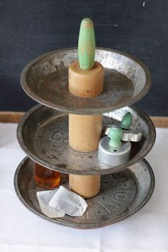 A tiered stand made from vintage pie plates, with a rolling pin center — made by Kaytie Yost, a.k.a.Seelamade on Etsy.  If you have a miter saw and an old rolling pin that's warped and/or cracked (i.e., no longer useful as a rolling pin!), you could try making your own caddy, like Jane of Mamie Jane's blog did. Jane's post about it is here.  Find more kitchen-related repurposing here.