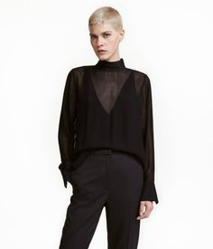 Black. Blouse in airy, crêped viscose fabric. Small stand-up collar, opening and snap fasteners at back of neck, and long sleeves with snap fasteners at