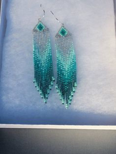 I used brick stitch (also known as cheyenne stitch) to make these earrings; they are my own pattern. * Ombre Earrings in Shades of Teal Green with Translucent Gray * Matching Teal Crystals on Bottom of Fringe * Super Lightweight * 4 Long - Including the Sterling Silver Ear-Wires