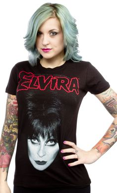 KREEPSVILLE BIG HAIR GIRLY TEE      $25.00    Every ghoul must check out this tee from Kreepsville's Elvira collection! This short sleeve, black girly tee features Elvira herself printed in the center with her name printed in red above her. 100% Cotton.    #Elvira #UpAllNight #Screamqueen #horror #pale #bighair #80s