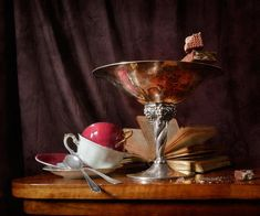 http://pixels.com/products/piece-of-wafer-in-chocolate-nikolay-panov-art-print.html Classic still life photography with white and pink porcelain coffee cups, silver vase with golden reflections, old book and pieces of wafers in chocolate on wooden tabletop in interior decoration