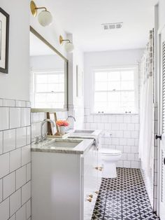 Besides garish pink tile, the bathroom's woes also included ancient plumbing and water damage. After a total rip-out, Hannah updated it with a black-and-white palette, using Amethyst Artisan cement floor tiles and square ceramic wall tiles outlined in black grout. Brass sconces from Cedar