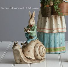 Resin garden rabbit riding on a snail.  Shop for unique home decor at Shelley B Home and Holiday.com