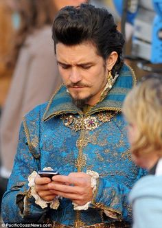 Orlando Bloom, in full 17th Century costume on the German set of the Three Musketeers in Germany, checking his Blackberry