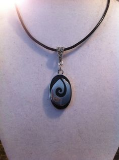 Unique wood pendant is outlined in silvertone steel and features a silvertone…