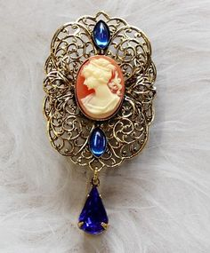 Adorable brooch cameo with blue stones Take a look at this Very Nice Brooch! This brooch is hanmade and measure: 64x31mm. Need more? Just