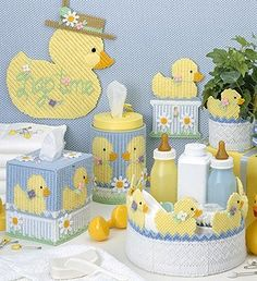 "Ducks for the Nursery Plastic Canvas ePattern - You'll love decorating the nursery with this sunny collection! Inspired by the popular rubber duck bath toy, these feathered friends make a splash on lots of cute accessories for baby's room. All pieces are stitched on 7 mesh plastic canvas using worsted weight yarn. The Baby Wipe Cover requires a 12"" x 18"" piece of canvas. The Divided Container requires a 9"" diameter canvas circle for the bottom. Number of Designs: 6 nursery accessories ..."