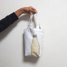 """食べ物の大きさに合わせてデザインしたバッグ""""FOODS""""シリーズのひとつで、 牛乳1リットルのパックが2本入るサイズになっています。  裏地はついていますが、ポケットはありません。 シンプルな綿素材のトートバッグです。  約H250×W240×マチ85mm (ハンドメイド製品につ..."""