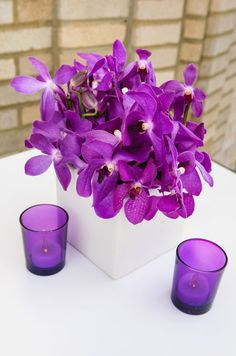 Pure purple orchids are paired with matching votive candles for a chic feel.