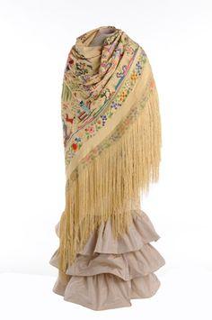 Este espectacular mantón de seda profusamente bordado presenta escenas cotidianas y motivos vegetales. Los rostros de los personajes son pla...