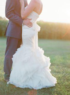 Ruffled train fit and flare wedding dress: http://www.stylemepretty.com/wisconsin-weddings/door-county/2016/02/10/rustic-glam-wisconsin-summer-wedding/ | Photography: The McCartneys - http://www.meetthemccartneys.com/