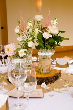 Rustic table centres using informal display of flowers, burlap, lace and trunk slices.  Photo taken by Eleanor of Interlace Photography