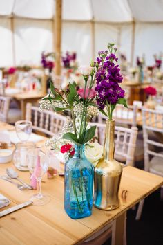 Scented stocks, roses, carnations and gysophila in pinks and purples gave a natural, wild feel to these table arrangements. Some bottles were painted gold, Summer wedding decor by Glass Slipper Weddings