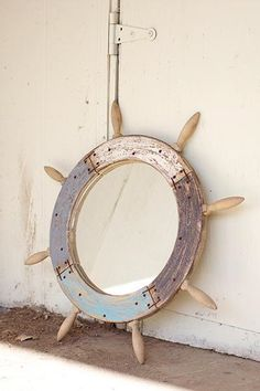 Ships Wheel Mirror. Reclaimed wood creates our unique Ships Wheel Mirror. Hand-painted and distressed; rusted screws and staples are intended to maintain the integrity of the reclaimed element. Each will be unique and vary due to the hand-made and natural nature.