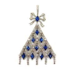 Belle epoque sapphire and diamond latticework pendant by Joseph Chaumet, Paris c.1905,  of triangular outline, the openwork diamond lattice hung with lozenge-cut sapphires, a fringe of rose cut diamond lines below, sapphire and diamond set ribbon bow surmount and diamond line suspension loop, millegrain set Length 5.4cm / 2 1/8'' Weight: 8.5g