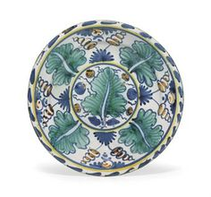 AN ENGLISH DELFT 'OAK-LEAF' CHARGER CIRCA 1680, POSSIBLY BRISTOL OR LONDON The center with a roundel painted with a large leaf surrounded by nuts or berries and radiating alternating leaves and paired tendrils growing from a tuft of grass, within a blue and yellow line and blue-dash rim, on a circular foot 13¼ in. (33.6 cm.) inches Glazed Pottery, Glazes For Pottery, Delft, Yellow Line, Blue And White, Moroccan Plates, English Pottery, Pottery Designs, Pottery Making