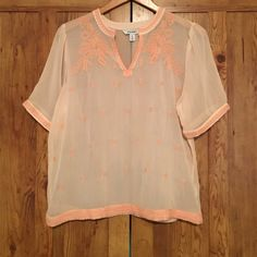 Old Navy shirt This shirt is so pretty. It's. Alight pink/peach with a darker version of that color for the borders and embroidery. Flowy top with super light see through material. There is a purple mark on the back of the shirt. I've never worn it so I must have bought it like that. Regardless, the shirt is very pretty. Put a pair of braided sandals and jean shorts with this. Old Navy Tops